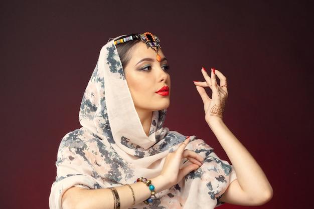 Mulher bonita em estilo oriental com mehendi no escuro