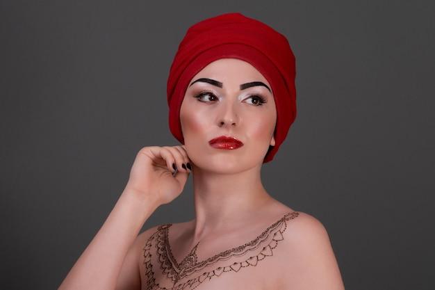 Mulher bonita em estilo oriental com mehndi em uma parede cinza