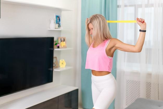 Mulher bonita em fazer roupas esportivas da moda fazer exercitar com faixa amarela em casa. exercícios em casa conceito