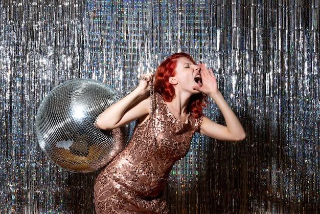 Mulher bonita em festa com bola de discoteca chamando cortinas brilhantes