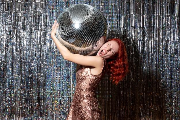 Mulher bonita em festa com bola de discoteca em cortinas brilhantes