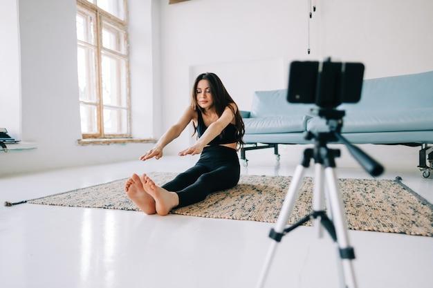Mulher bonita em fitness fazendo exercícios de alongamento na frente da câmera no tripé dentro de casa em casa