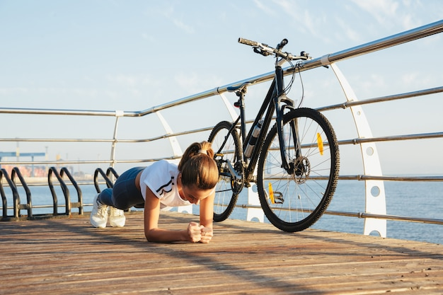 Mulher bonita em fitness fazendo exercícios de prancha na praia, andando de bicicleta