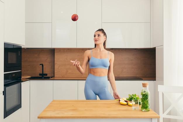 Mulher bonita em fitness preparando comida saudável em casa, segurando uma maçã