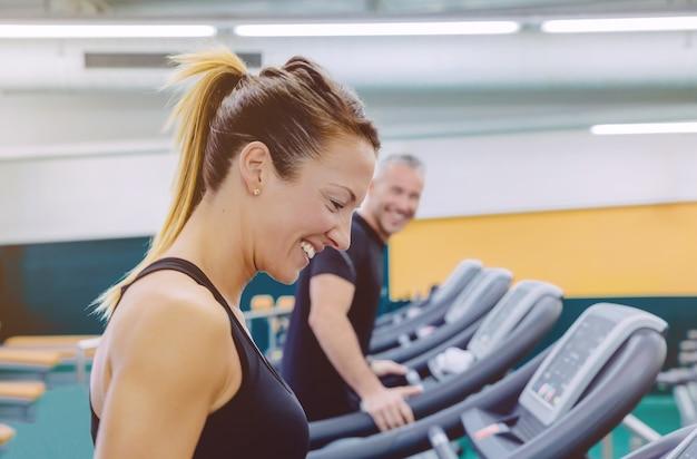 Mulher bonita em fitness rindo com um amigo em uma esteira para treinar na academia