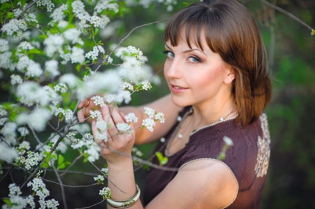 Mulher bonita em flores brancas na primavera