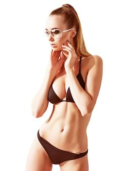 Mulher bonita, em forma e esportiva em um maiô. conceito de perda de gordura, lipoaspiração e remoção de celulite.