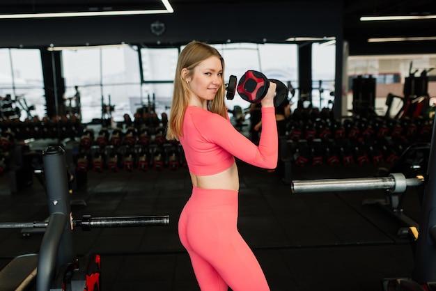 Mulher bonita em forma muscular exercitando-se, construindo músculos na academia