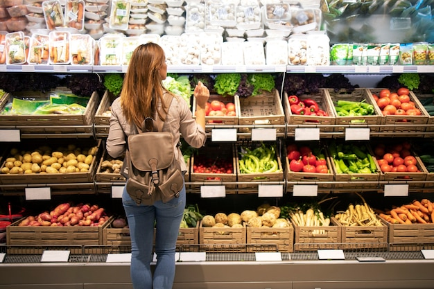 Mulher bonita em frente a prateleiras de vegetais, escolhendo o que comprar