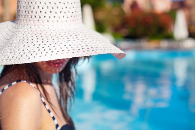 Mulher bonita em grande chapéu branco perto de piscina em dia ensolarado