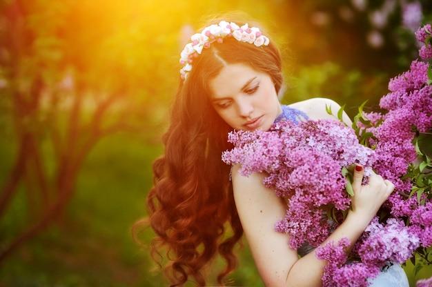 Mulher bonita em grinalda de flores com uma flor lilás no pôr do sol