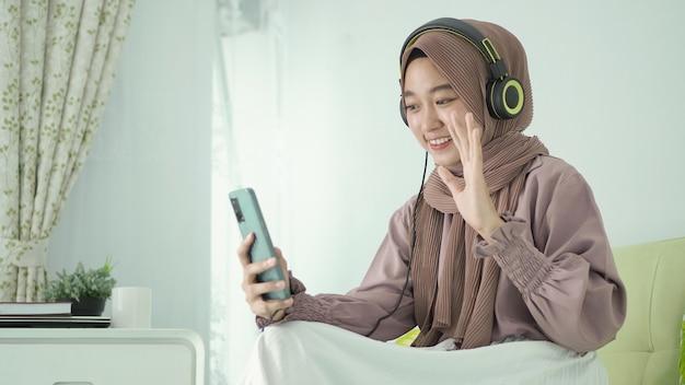 Mulher bonita em hijab cumprimentando felizmente por videochamada em casa