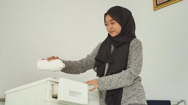 Mulher bonita em hijab derrama detergente para a roupa em casa