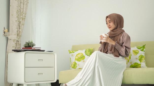 Mulher bonita em hijab sentada relaxada tomando uma bebida