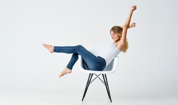 Mulher bonita em jeans fica em uma cadeira de fundo isolado glamour da moda