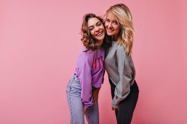 Mulher bonita em jeans vintage rindo com a irmã. retrato interior de garotas alegres em pé rosa com um sorriso.