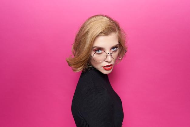 Mulher bonita em lábios vermelhos de suéter preto em fundo rosa de emoções de óculos.