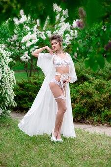 Mulher bonita em lingerie branca ao ar livre. sexualidade.