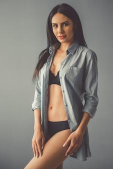 Mulher bonita em lingerie preta e camisa desabotoada.