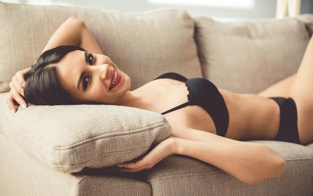 Mulher bonita em lingerie preta está olhando para a câmera