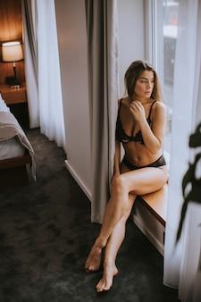 Mulher bonita em lingerie sentado e olhando pela janela em seu lindo apartamento