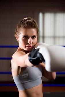 Mulher bonita em luvas de boxe brancas no ringue no treinamento.