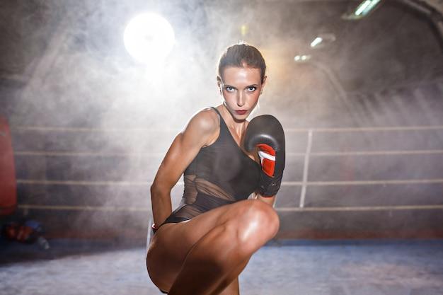 Mulher bonita em luvas de boxe, pronta para chutar