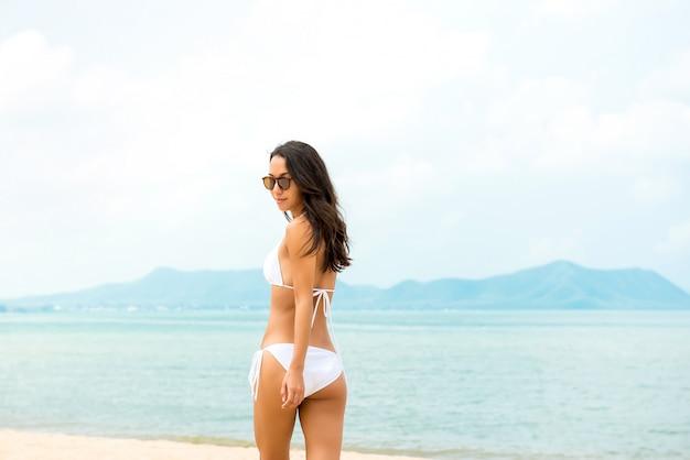 Mulher bonita em maiô biquíni branco na praia no verão