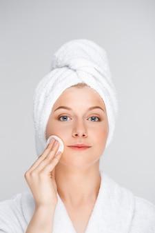 Mulher bonita em maquiagem de decolagem de roupão com esponja