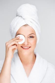 Mulher bonita em maquiagem de decolagem de roupão de banho com limpador