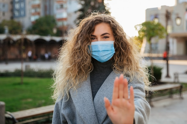 Mulher bonita em máscara facial de proteção contra vírus, mostrando o gesto de parar a infecção. pandemia de coronavirus covid-19 e conceito de saúde. precauções com o coronavírus