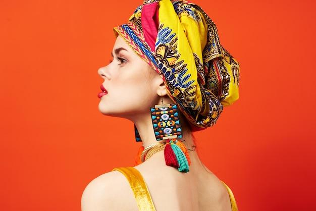 Mulher bonita em modelo de estúdio de joias com turbante multicolorido