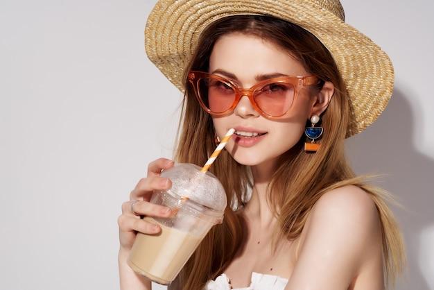 Mulher bonita em óculos da moda suando com estúdio de charme de bebida