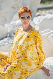 Mulher bonita em óculos de sol com vestido amarelo na areia de muito calor