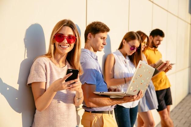 Mulher bonita em óculos de sol cor-de-rosa que sorri na câmera e que usa o telefone celular.