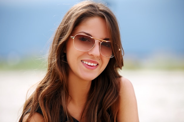 Mulher bonita em óculos de sol na praia