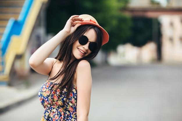 Mulher bonita em óculos de sol posando na cidade