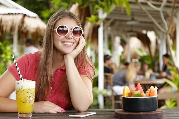 Mulher bonita em óculos de sol redondos, aproveitando o feriado há muito aguardado em um país tropical, tomando coquetel de frutas, apoiando o cotovelo na mesa do café com o celular nele, tendo uma expressão alegre e relaxada