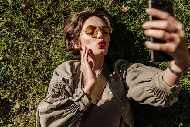 Mulher bonita em óculos de sol redondos e jaqueta encontra-se na grama e sopra beijo lá fora. jovem mulher com cabelo curto, tomando selfie ao ar livre.