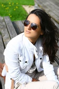 Mulher bonita em óculos de sol relaxantes ao ar livre