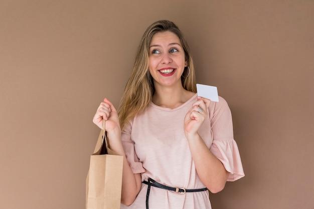 Mulher bonita em pé com a sacola de compras e cartão de crédito