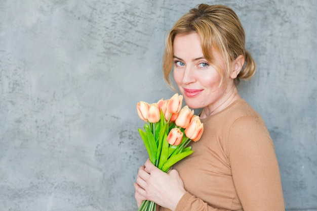 Mulher bonita em pé com buquê de tulipas