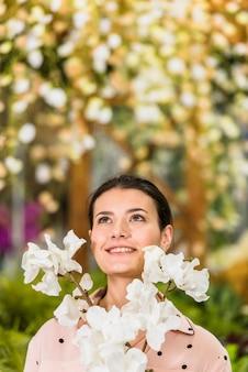 Mulher bonita em pé com flores brancas