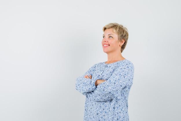 Mulher bonita em pé com os braços cruzados na blusa estampada e olhando positiva. espaço para texto