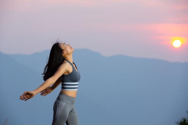 Mulher bonita em pé com os braços na montanha ao pôr do sol