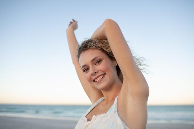 Mulher bonita em pé com os braços para cima na praia