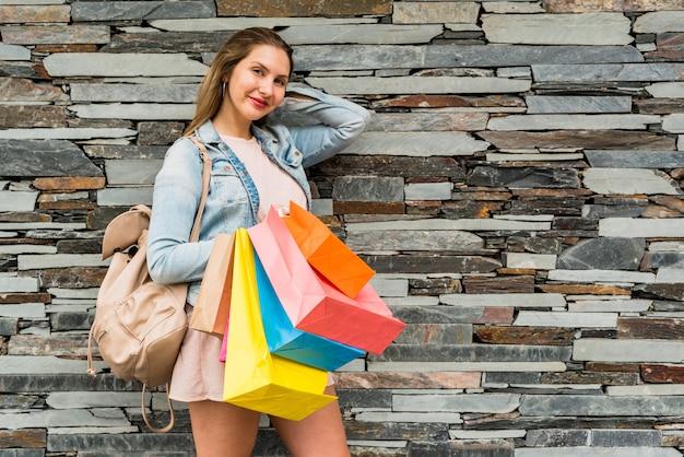 Mulher bonita em pé com sacolas coloridas