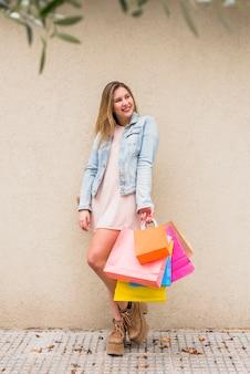 Mulher bonita em pé com sacolas de compras fora