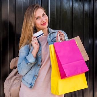 Mulher bonita em pé com sacos de compras e cartão de crédito na parede