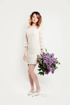 Mulher bonita em pé com um grande buquê de flores da primavera